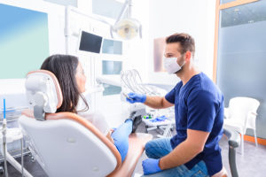 a woman at the dentist office about to undergo oral cancer screenings