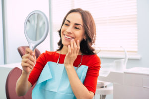a woman inspecting her gums after periodontal disease treatment