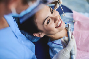 a woman at the dentist smiling because she has good oral hygiene