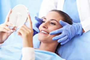 a woman looking at her brand new dental crowns in a mirror
