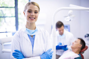 a female dentist getting ready to conduct pinhole surgical technique
